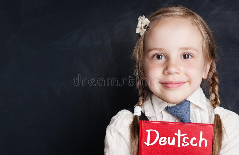 Kids learn German. Curious child girl with german book royalty free stock photo