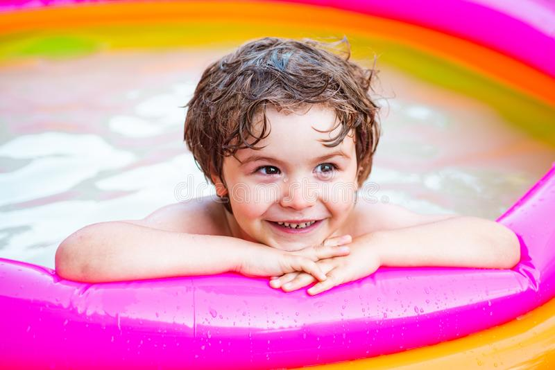 Kids learn to swim. Enjoying in swimming pool. Boy happy swimming in a pool. Child having fun in summertime. Summer stock images