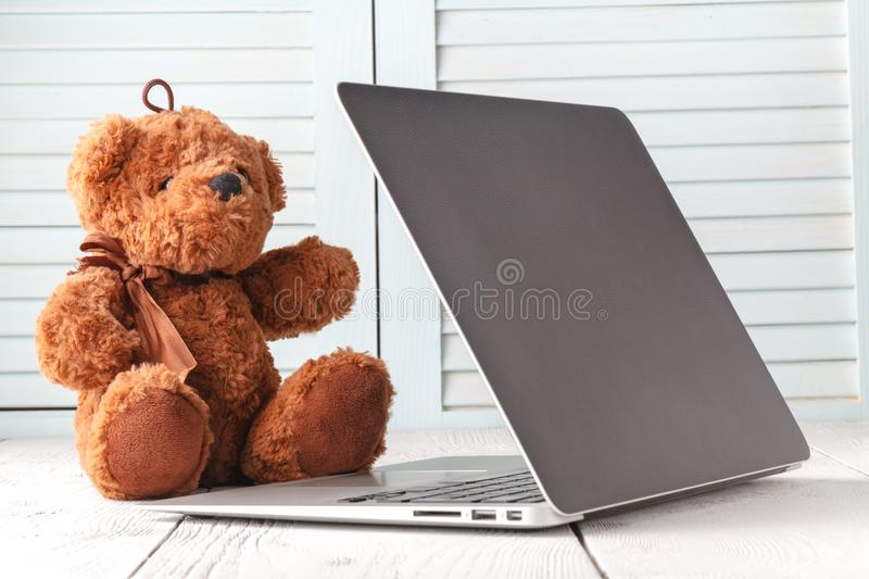 Kids learning, teddy bear with laptop royalty free stock photo