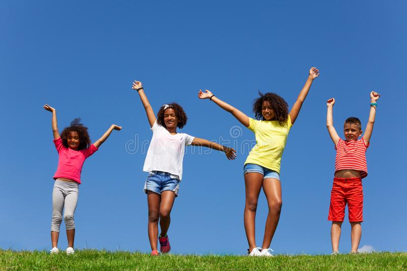 Kids with lift hands stand in park over clean sky stock image