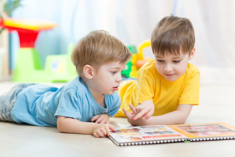 Kids looking at book in playschool or nursery stock photography
