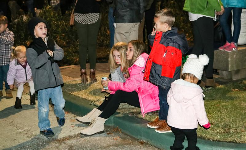 Kids looking at phone and playing at Christmas lighting ceremony in Tulsa Oklahoma USA 11-23-2017 royalty free stock photo