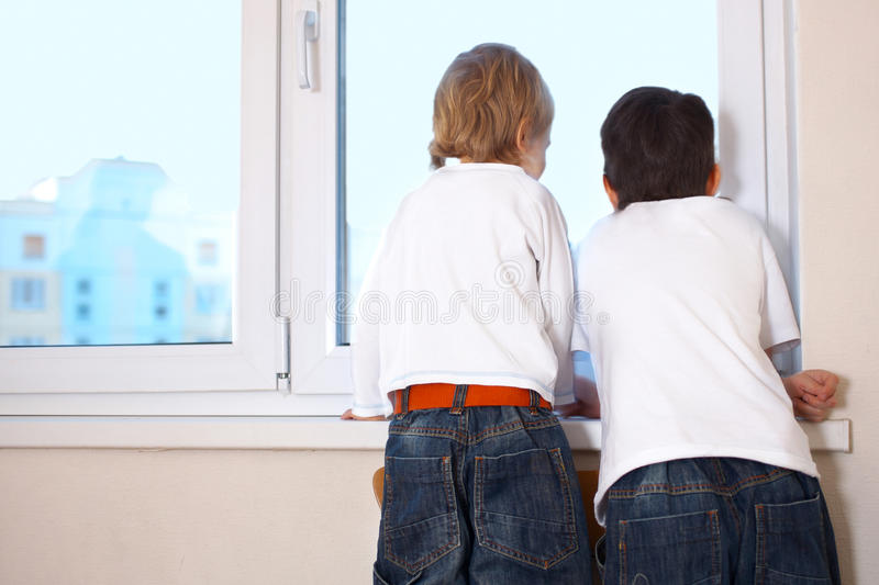 Kids looking at window. Two kids looking at window royalty free stock photography