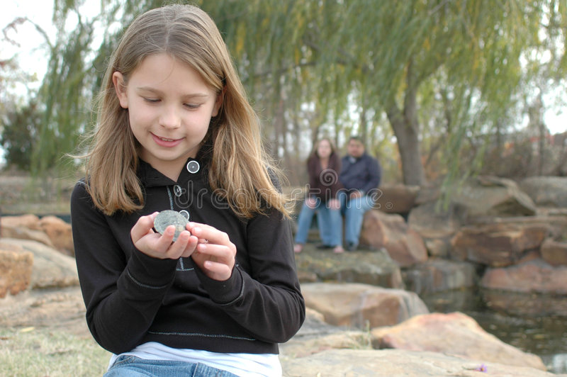 Kids love animals. Happy little girl sitting on a rock holding a small turtle while her parents sit behind her stock photos