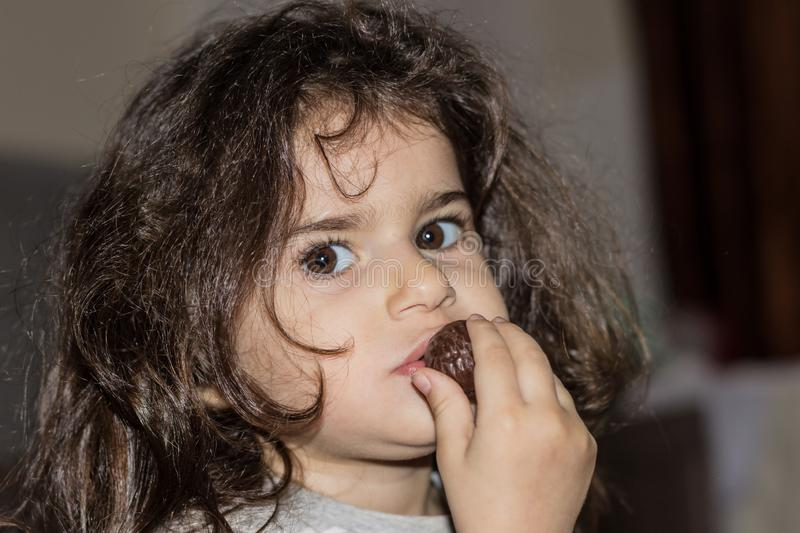 Close-up portrait of a little girl with curly hair. The child eats chocolate candy. royalty free stock photos