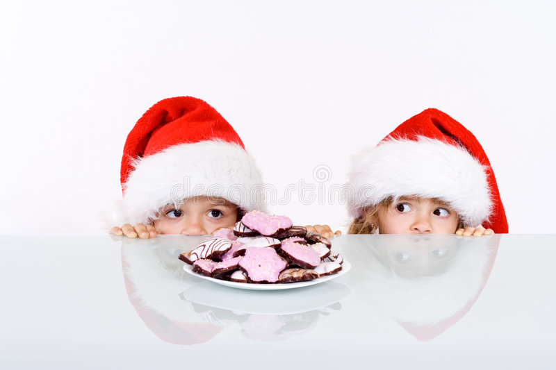 Kids lurking to get a glimpse of santa. Having gingerbread cookies as bait - on white background royalty free stock images