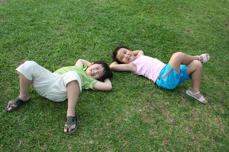 Kids lying on the grass stock photo