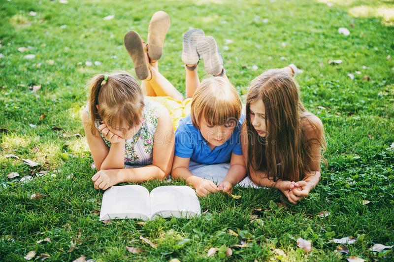 Kids lying on green grass and reading story book. Group of three kids lying on green grass and reading story book together. Education for children royalty free stock photos