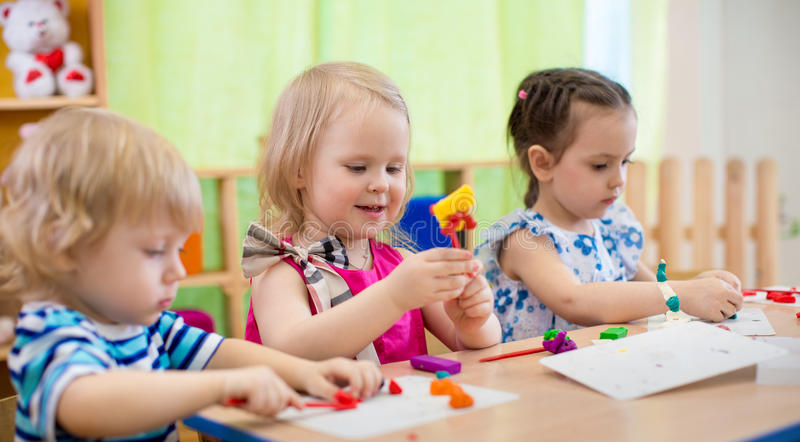 Kids making arts and crafts. Children in kindergarten. royalty free stock photography