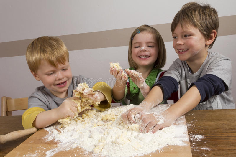 Kids making dough. For baking christmas cookies stock images
