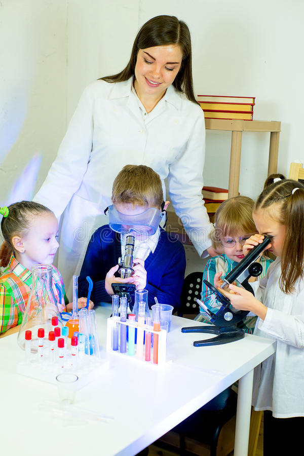 Kids making science experiments. With their teacher in laboratory. education stock images
