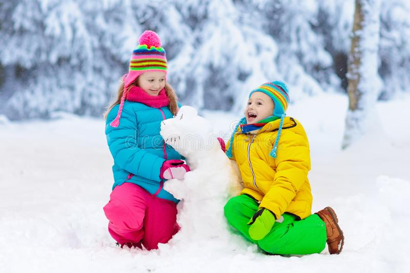 Kids making winter snowman. Children play in snow. stock photos