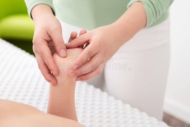 Kids massage. Young female massage therapist giving a 6 year old boy hand massage. Physical therapy, reflexology, osteopathy. Kids massage. Young female massage royalty free stock image