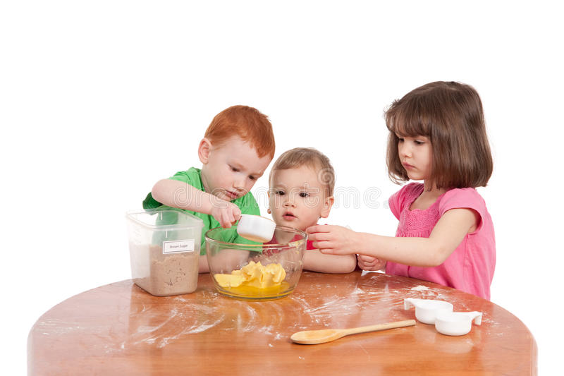 Kids measuring ingredients for baking in kitchen royalty free stock images
