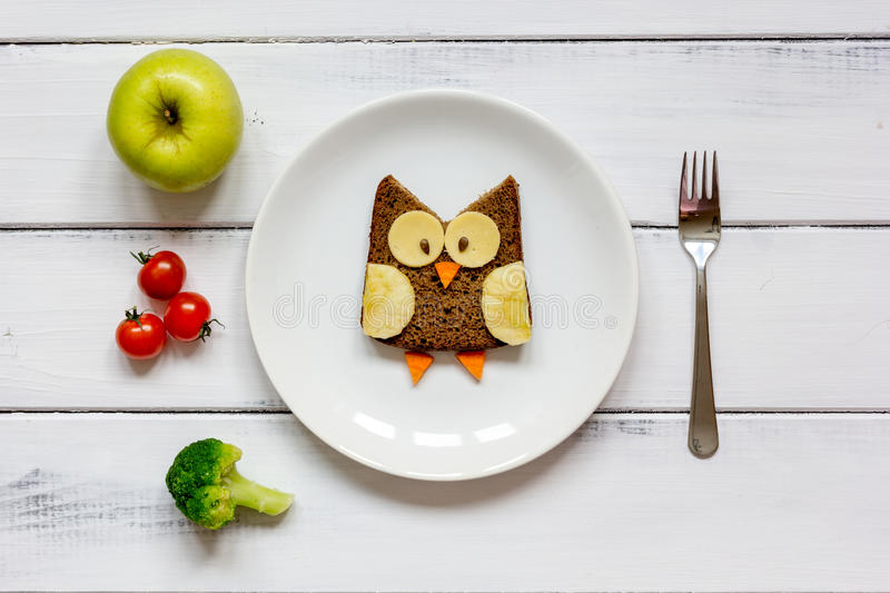 Kids menu owl shaped sandwich with vegetables and fruits stock photos