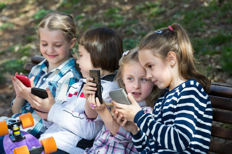 Kids with mobile devices outdoor. Happy children sitting on bench and playing with mobile devices royalty free stock photo