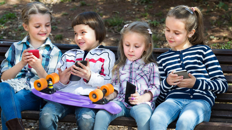 Kids with mobile devices outdoor. Smiling kids sitting on bench with mobile devices in street royalty free stock images