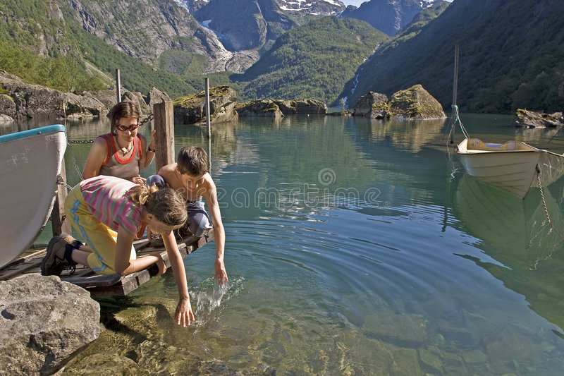 Kids with mother at lake royalty free stock photo