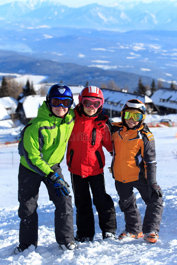 Kids on mountain slope in snow royalty free stock image