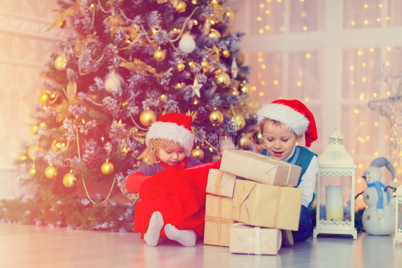 Kids opening christmas presents in decorated living room stock photo