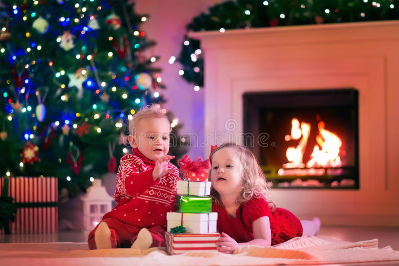 Kids Opening Christmas Presents At Fire Place Stock Image - Image of ...