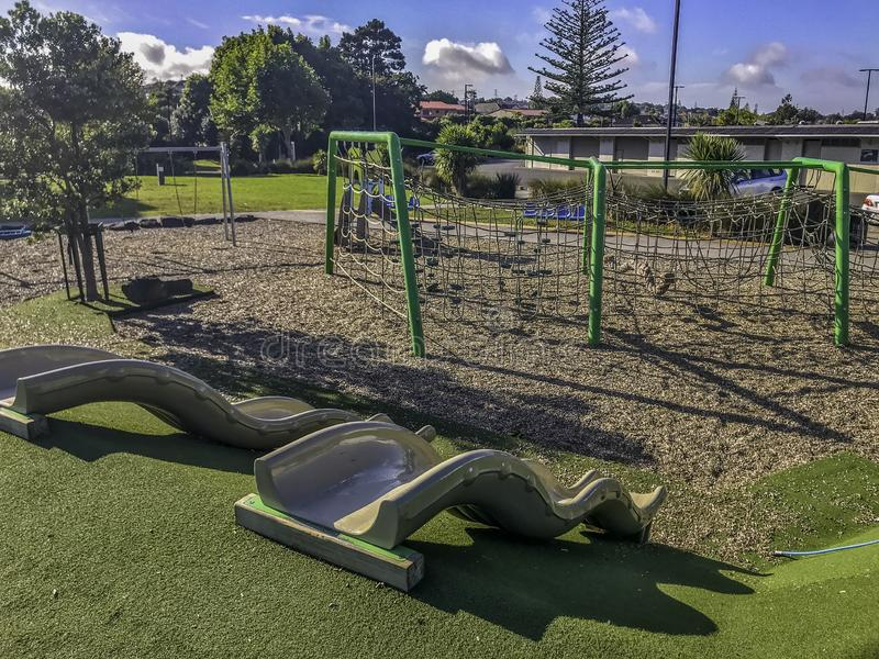 Kids outdoor play area. Outdoor play area for children including two slides,swings,climbing ropes on a warm bright sunny day among green trees stock photography