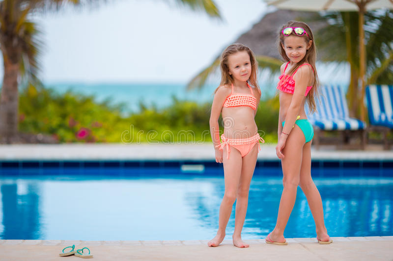 Kids in outdoor swimming pool on summer vacation. Adorable little girls playing in outdoor swimming pool royalty free stock photography