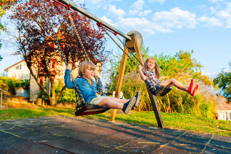 Kids outdoors. Adorable kids having fun outdoors on sunset, playing on a swing royalty free stock photos