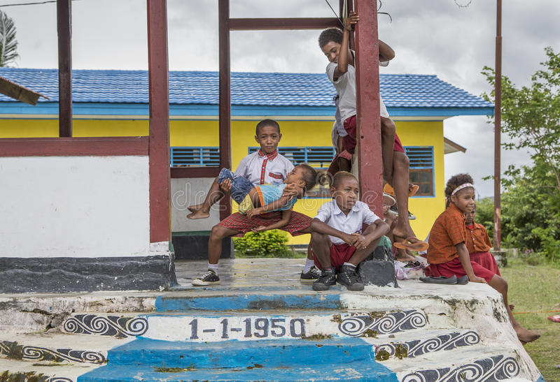 Kids outside a school in Jayapura. Jayapura, West Papua, Indonesia, February 17th, 2016: Schoolkids resting outside a school house royalty free stock image