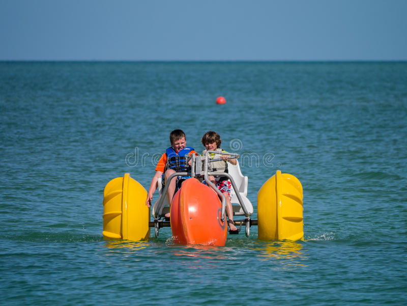 Kids with paddle boat on the ocean. Two young boys paddling a large paddle boat off the coast of Bonita Springs, Florida stock photography