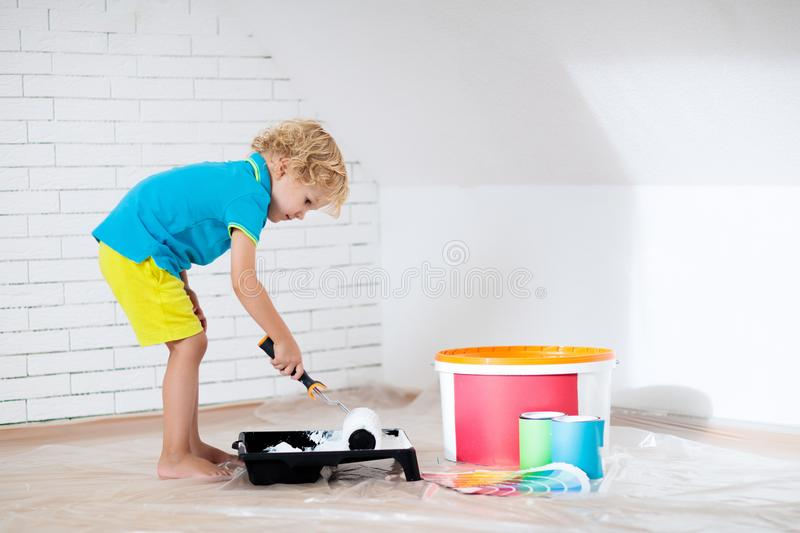 Kids painting attic wall. Home improvement. Kids painting attic wall. Home improvement and renovation. Child applying white paint on brick walls in bedroom royalty free stock images