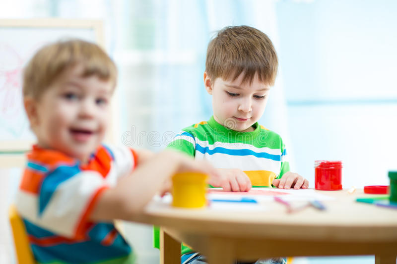 Kids painting in daycare or nursery or playschool. Kids boys painting in daycare or nursery or playschool stock images