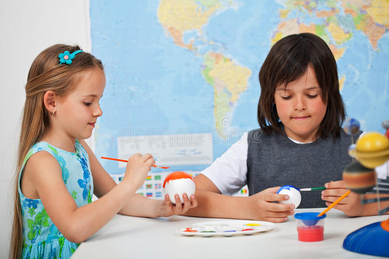 Kids painting the planets - for a solar system scale model royalty free stock images