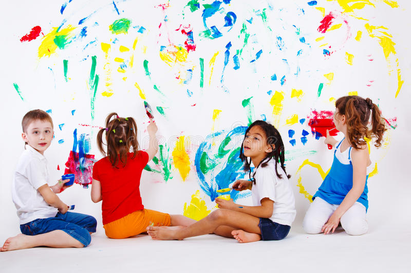 Kids painting the wall. Four preschool kids painting the wall stock photo