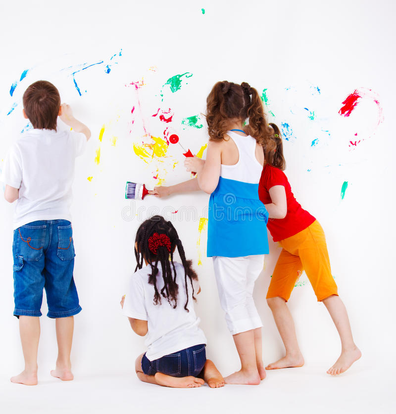 Kids painting wall. Four elementary aged kids painting wall stock photos