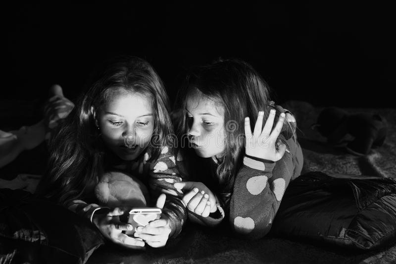 Kids in pajamas watch movie on phone on dark background. Party and fun concept. Schoolgirls have pajama party. royalty free stock images