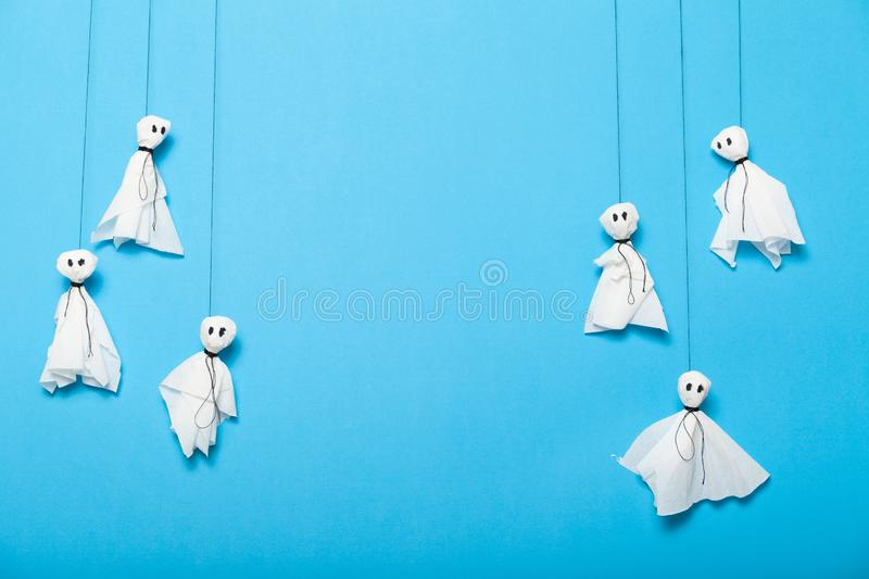 Kids paper ghosts artwork. Autumn halloween celebrating. Copy space for text royalty free stock photo