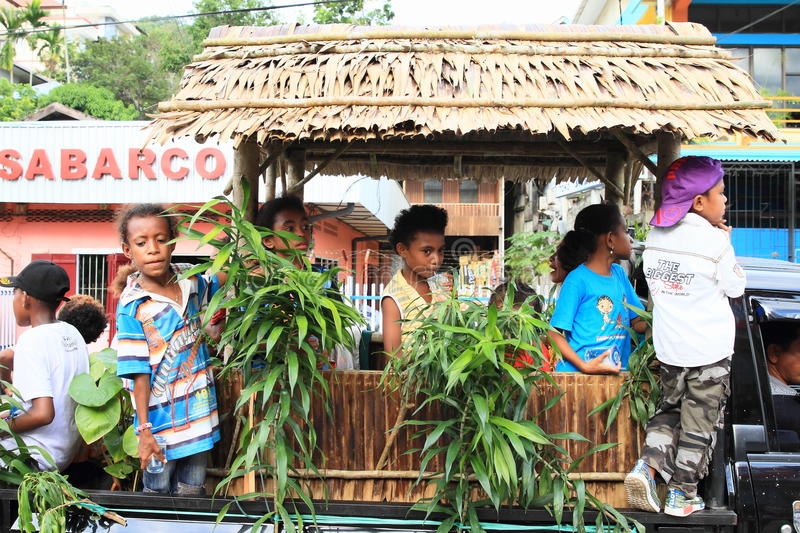Kids on parade float of Wondama - Papua Barat. Kids on parade float with hut from Wondama - Papua Barat with sign in procession in occasion of celebration of royalty free stock image