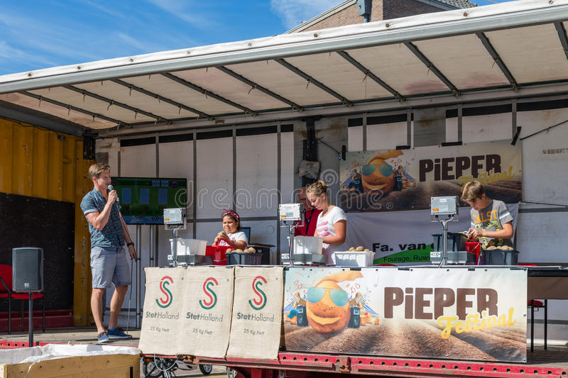 Kids peeling potatoes at a Dutch agricultural potato festival. EMMELOORD, THE NETHERLANDS - SEP 10: Competition of kids peeling potatoes at an agricultural royalty free stock image