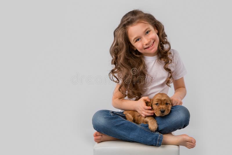 Kids pet friendship concept - little girl with red puppy isolated on white background stock photo
