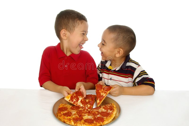 Kids and pizza. Two young hispanic brothers ready to eat a pepperoni pizza royalty free stock photo