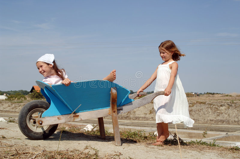 Kids at play. Two kids playing in a weel barrow