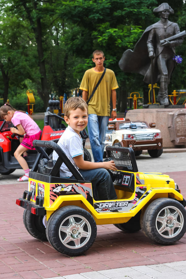 Kids in the play area riding a toy car. Nikolaev, Ukraine. NIKOLAEV, UKRAINE - June 21, 2014: Kids in the play area riding a toy car royalty free stock image