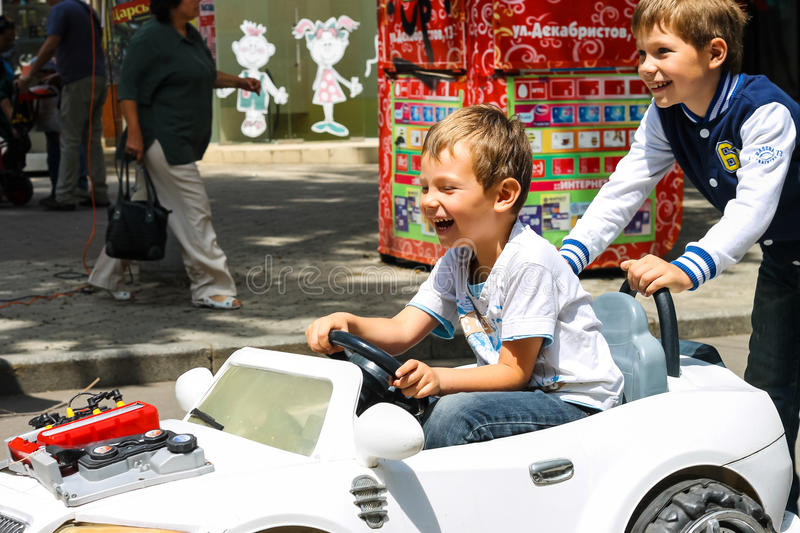 Kids in the play area riding a toy car. Nikolaev, Ukraine. NIKOLAEV, UKRAINE - June 21, 2014: Kids in the play area riding a toy car royalty free stock photography