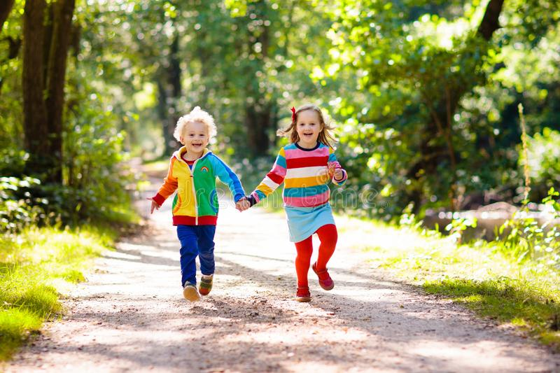 Kids play in autumn park. Children hiking in forest and mountains. Kids play outdoor in summer. Little boy and girl on hike trail in national park. Outdoor fun royalty free stock image