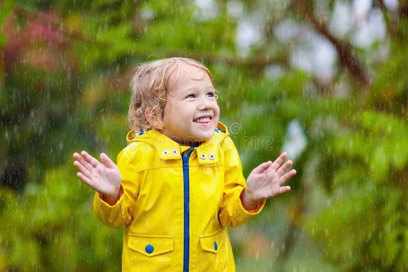Kids play in autumn rain. Child on rainy day stock photography