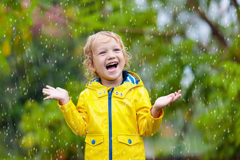 Kids play in autumn rain. Child on rainy day royalty free stock photo