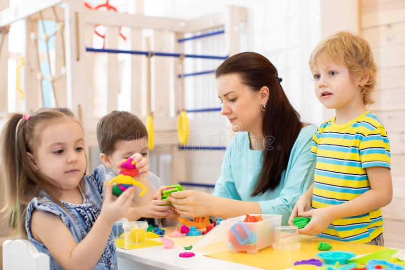 Kids with play clay toys in kindergarten stock images