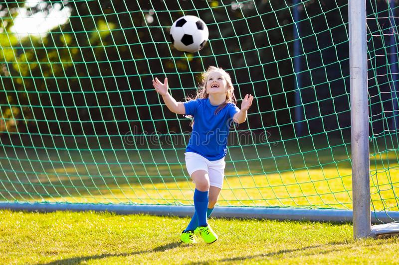 Kids play football. Child at soccer field. Kids play football on outdoor field. Children score a goal at soccer game. Little girl kicking ball. Running child in stock images
