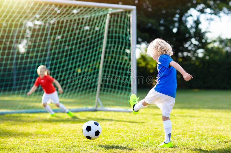 Kids play football. Child at soccer field. Kids play football on outdoor field. Children score a goal during soccer game. Little boy kicking ball. Running child stock image
